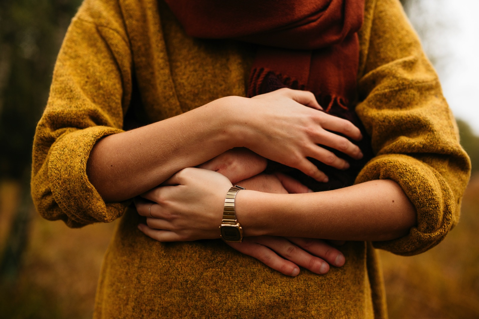 Couple's arms wrapped around stomach of woman