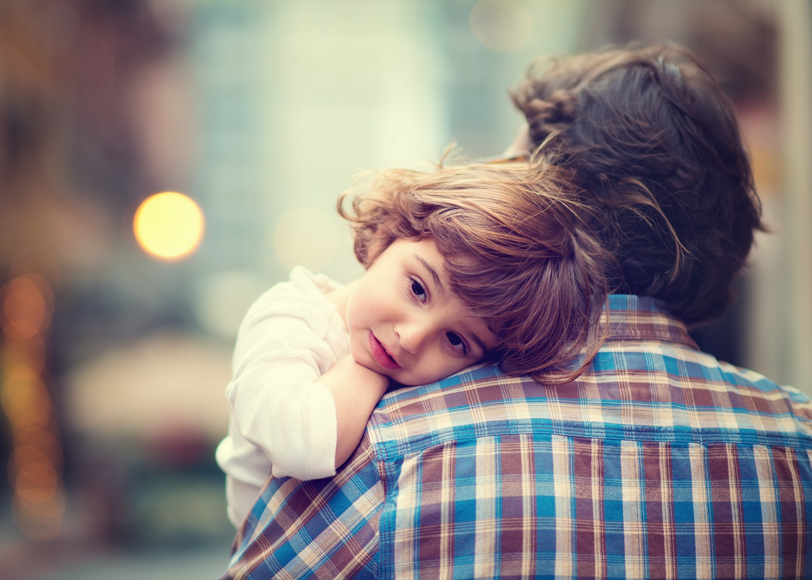 Young child resting head on man's shoulder