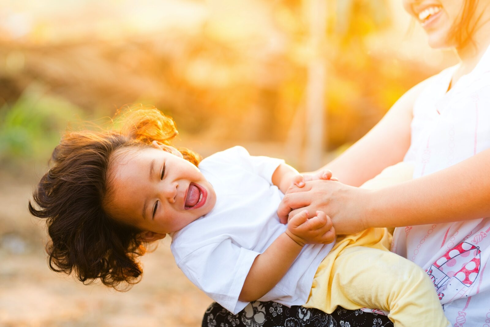 Laughing child leaning back on woman's knee